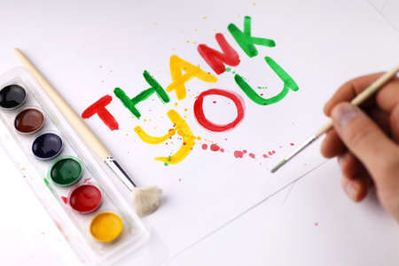 white sheet: inscription on a white sheet of paper with watercolors Thank you