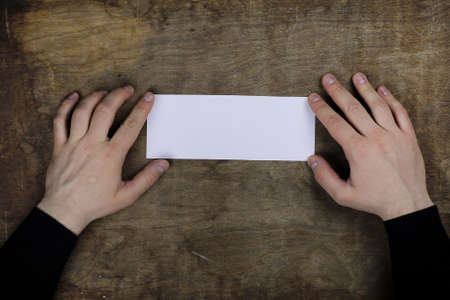 white sheet: male hands holding a white blank sheet of paper on the background of wooden texture table