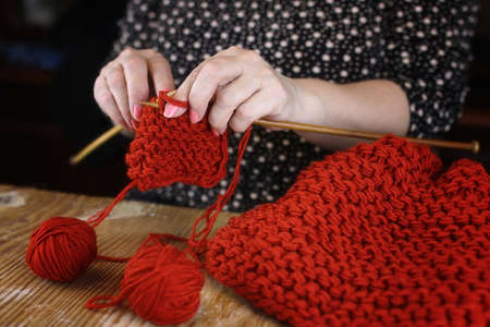 elderly woman is engaged in knitting warm sweaters for her grandchildrens