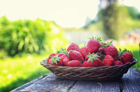 pawns: Strawberry in wicker plate on wooden background Stock Photo
