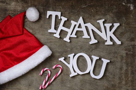 red santa hat on a textured wooden background and Thank you wooden white letters
