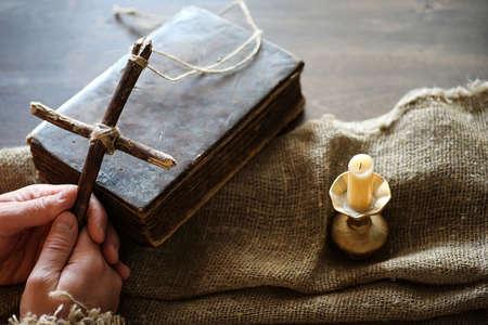 古代の宗教的な本と木製の背景と黄麻布の木製の十字架