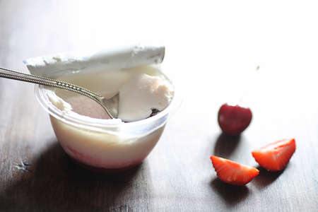 Yoghurt with fresh juicy strawberries and cherries on a wooden table