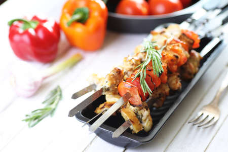 Kebab cooked on metal skewers with vegetables served on white table