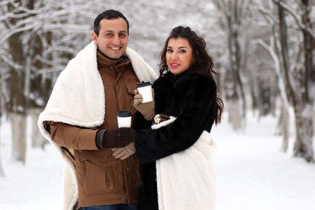 A young couple walk in a winter park Stock Photo