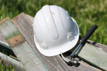 Construction materials lie on the grass hammer and helmet