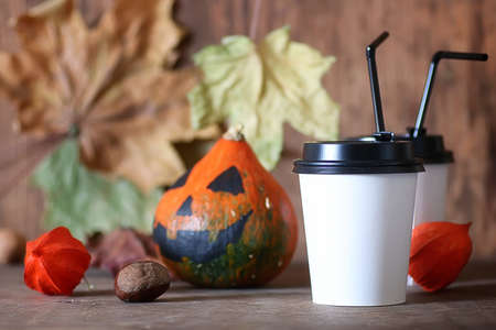 Coffee paper cup on the table with pumpkin