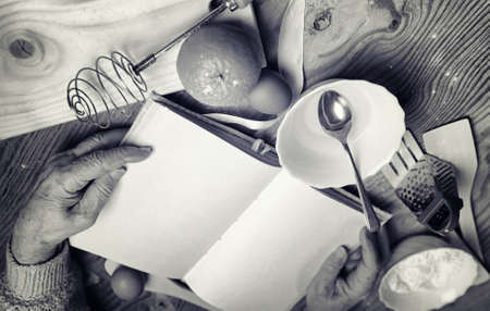 Open recipe book in the hands of an elderly woman in front of a table with utensils Stock Photo