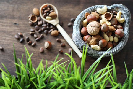 Various useful and tasty nuts on a wooden table and pots with green grass Stock Photo