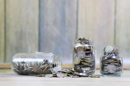 Accumulated coins stacked in glass jars on the floor Stock Photo