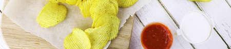 bakground: Horizontal bakground of potato chips on a white table Stock Photo