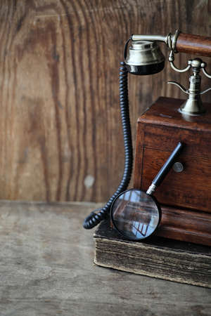 waiting phone call: Old telephone and retro book on a wooden table