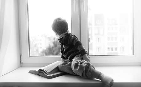 The little boy is reading a book. The child sits at the window a
