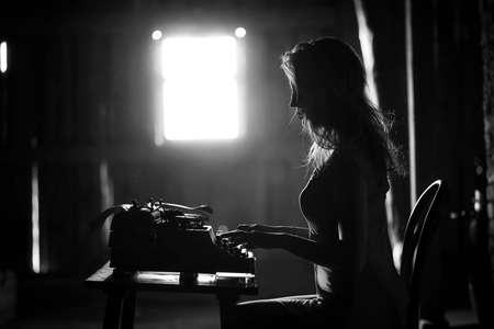 A girl prints on an old typewriter Reklamní fotografie