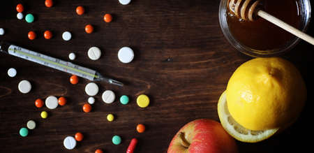 Drugs and pills on a wooden table. Various means to prevent cold