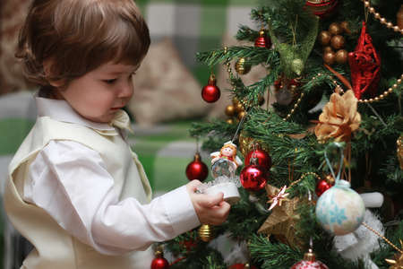 child decorate the Christmas tree toy