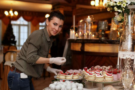 woman arranging festive table with sweets and a variety of sweet snacks