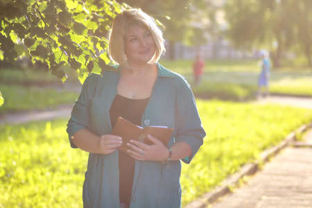 woman holding a book in the park Stock Photo