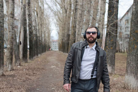 man with beard and headphones in the park