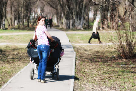 A young mother with a stroller walking in a park in autumn