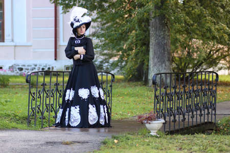 A woman in a classic eighteen century dress with a book on the bridge in the park