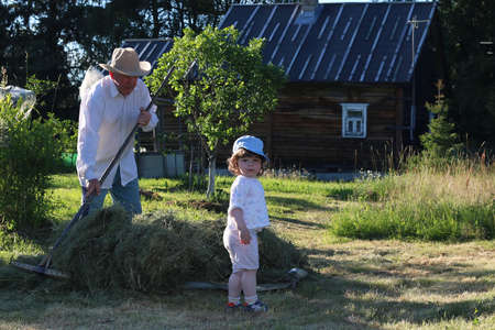 A child and a grandfather in a field in a rural area