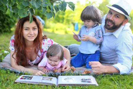 A family lying on the grass outdoor