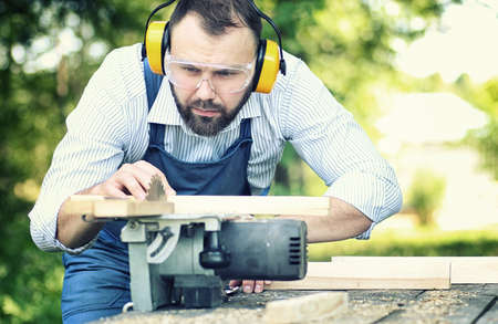A bearded man working with a circular saw Stock Photo