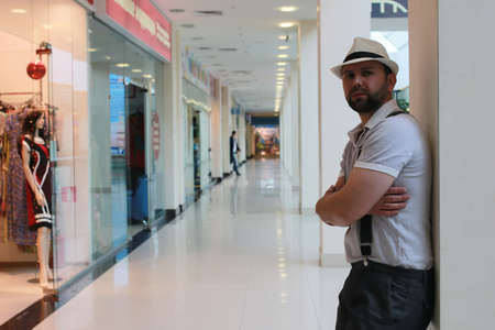A bearded man wearing a hat and suspender posing indoor in a mall