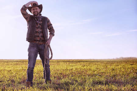 A cowboy standing in a field during sunset Stock Photo