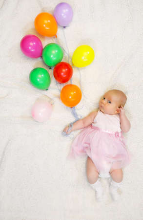 little girl holding a bunch of balloons and flight shows Stock Photo