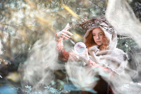 A red-haired witch doing a ritual with a crystal ball in a dense forest 스톡 콘텐츠