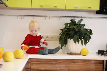 A cute baby sitting on the kitchen's counter