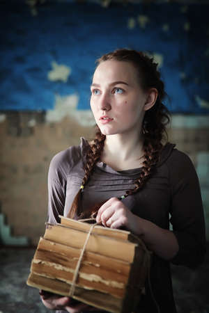 A girl with old books in the old house Stock Photo
