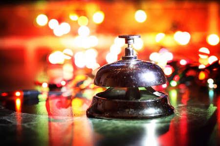 reception bell on table and color shining garland on background Stock Photo