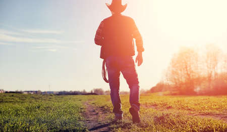 A man cowboy hat and a loso in the field. American farmer in a f