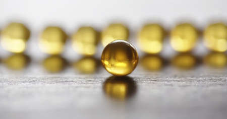 Fish fat. Medical products for the treatment of diseases. The concept of health dependence on tablets. Capsules of fish oil on wooden background.