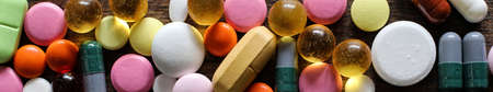 Medical background of various colorful medications on a textured wooden