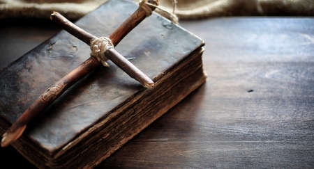 Religious old book on a wooden table. A religious cross tied with a rope and burlap next to bible. Worship, sins and prayer.