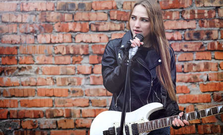 Beautiful young girl rocker with electric guitar. A rock musicia
