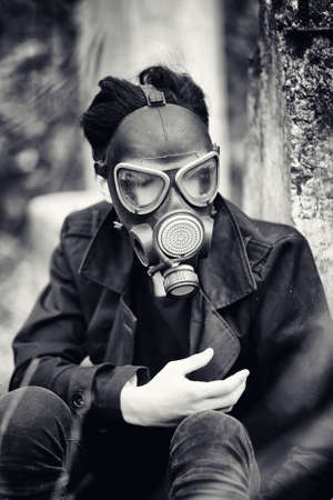 radiation protection suit: The guy in the coat and gas mask. Post-apocalyptic portrait Asian masked from radiation. The boy is Korean in a mask from poisoning with gases. Post-nuclear mask on the Asian.