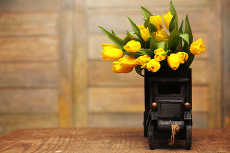 A bouquet of yellow tulips in a vase on the floor. A gift to a w