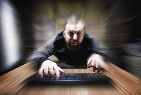 The hacker in the hood sits and works Stock Photo