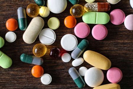 Medications on a textured wooden background Stock Photo