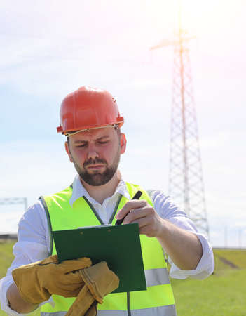 An electrician in the fields near the power transmission line. T Stock Photo