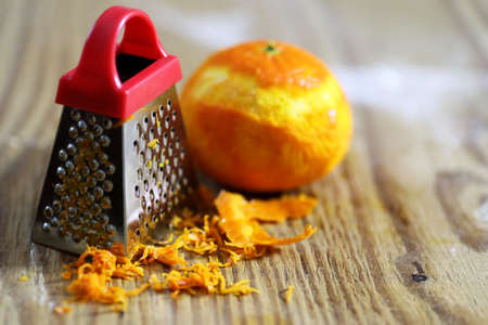 grater zest of citrus fruit and on the wooden table
