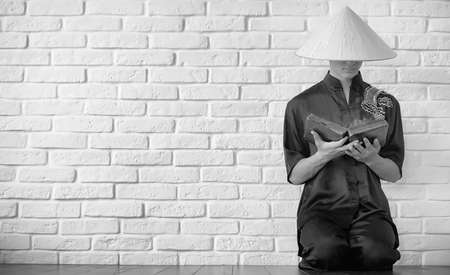Asian young novice on a white brick wall background