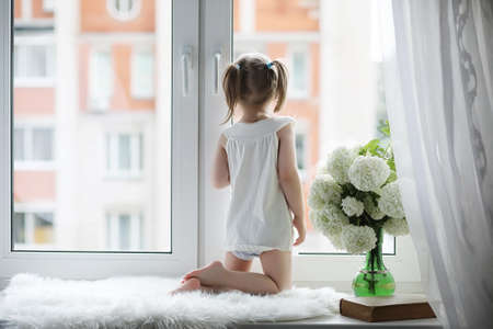 A little girl is sitting on the windowsill. A bouquet of flowers in a vase by the window and a girl sniffing flowers. A little princess in a white dress with a bouquet of white Stock Photo