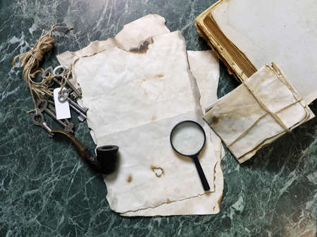 retro papers and book on detective work table with tools Stock Photo