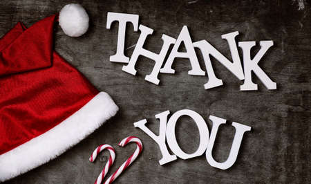 red santa hat and letters thank you on grey textured wooden back
